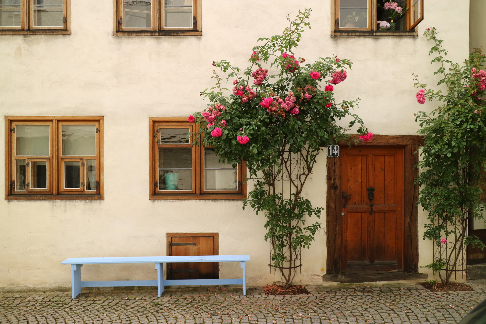 an old house with flowers and a bench in front of it