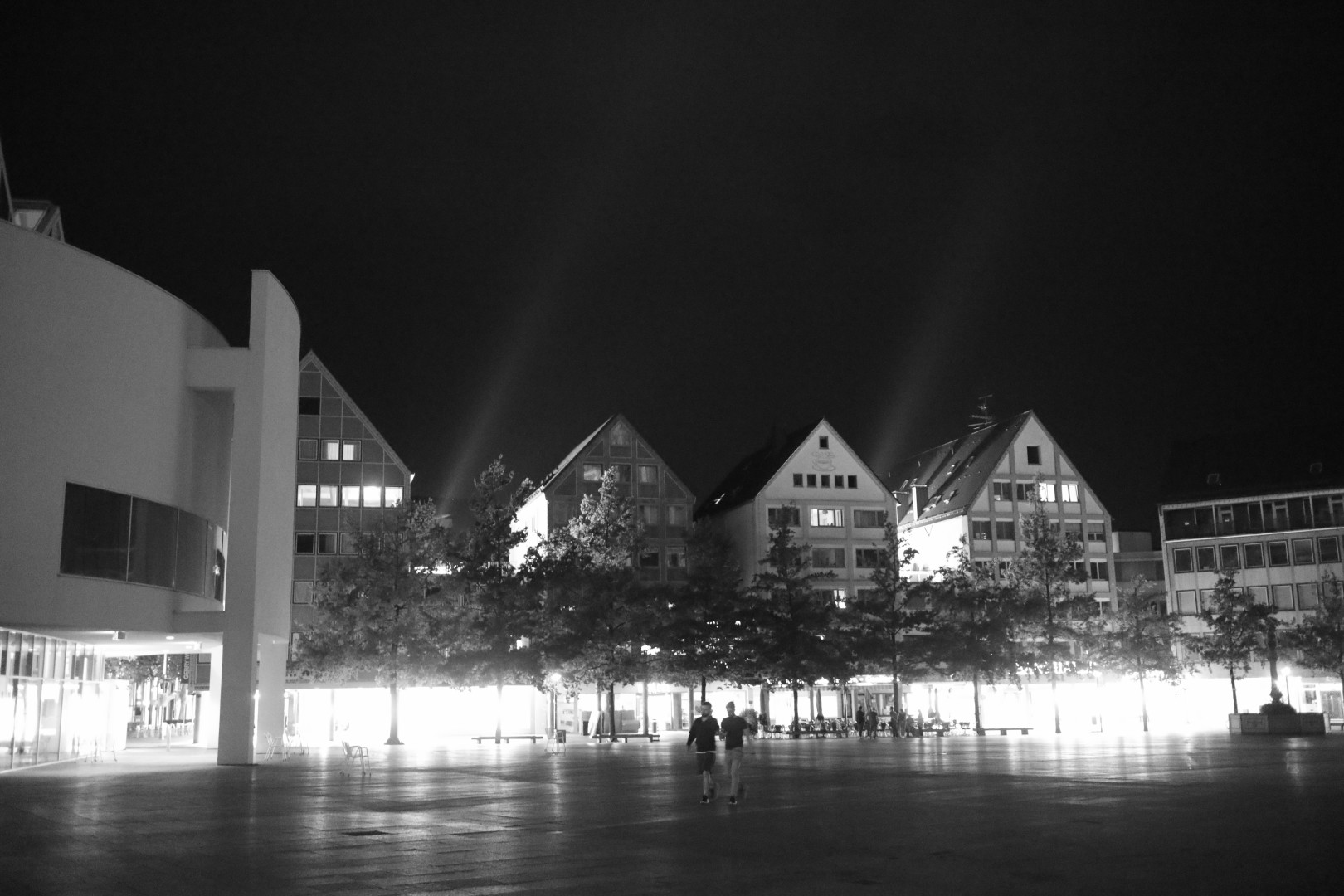 b/w pic of houses at night with lights streaming upwards