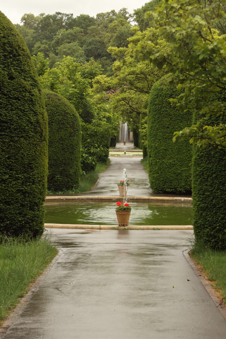 a view along a path in a palatial garden between hedges, 3 ponds with 2 fountains. No humans.